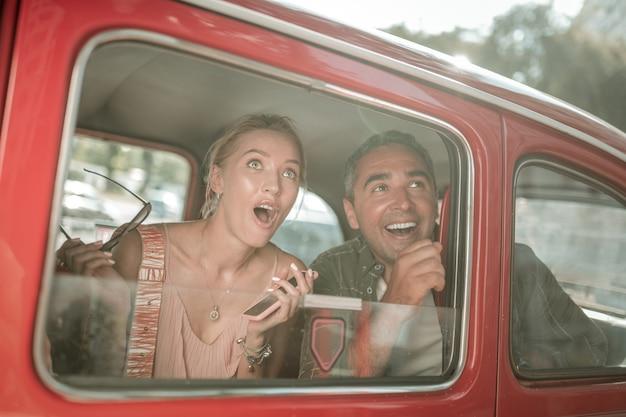 이것만 봐. 놀란 여자가 남편과 함께 차에 앉아 입을 벌리고 창밖을 바라보고 있다.
