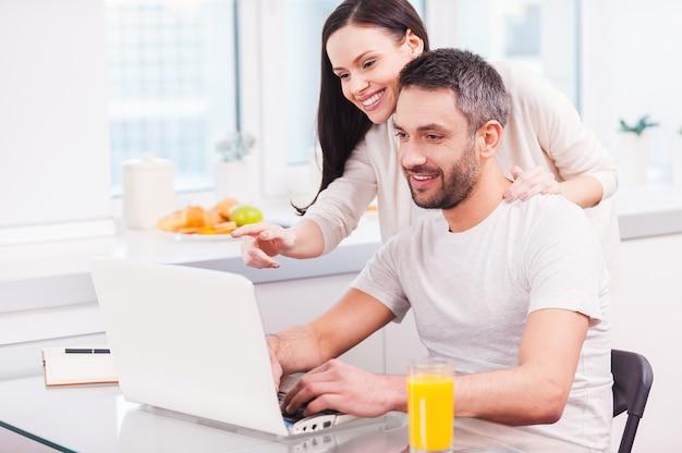 이것만 봐! 그의 쾌활한 여자 친구가 그와 결합하고 모니터를 가리키는 동안 노트북에서 일하고 웃는 잘 생긴 젊은 남자