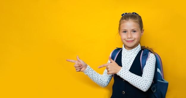 이것 좀보세요. 노란색에서 행복 한 작은 학교 소녀 가리키는 손가락