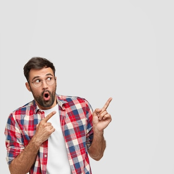 Just look here! vertical shot of amazed bearded man points with both index fingers at upper right corner, shows something incredible, dressed casually, isolated over white wall. pay attention to this
