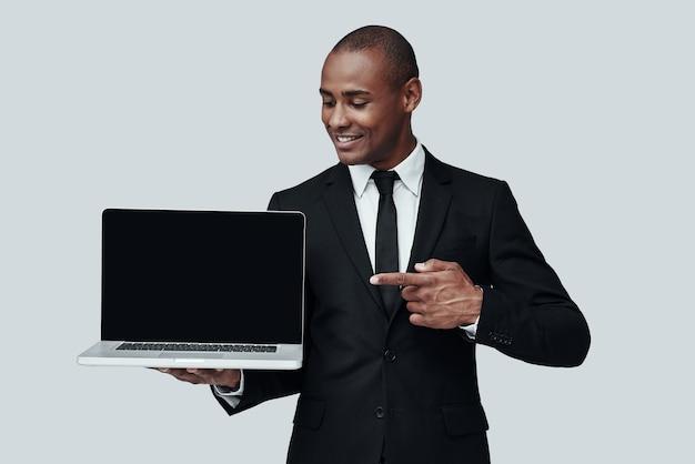 여기만 봐! 노트북을 가리키고 회색 배경에 서서 웃고 있는 정장 차림의 젊은 아프리카 남자