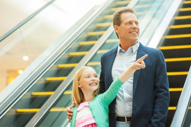 あそこを見てください!陽気な父と娘がエスカレーターで下に移動し、小さな女の子が指差して笑っている