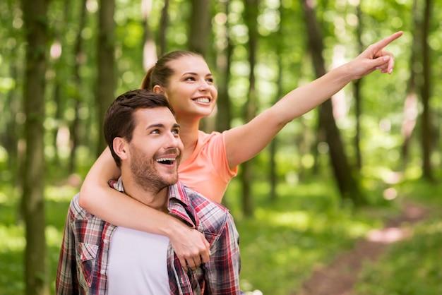 저기만 봐! 여자가 남자를 껴안고 미소로 가리키는 동안 공원에서 산책하는 행복한 젊은 사랑의 커플