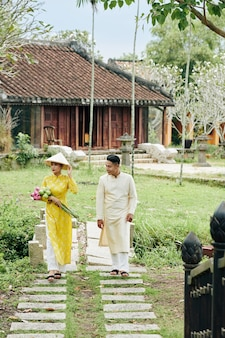 결혼식 후 정원에서 걷는 전통 드레스를 입은 아름다운 베트남 커플과 결혼했습니다.