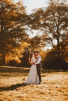 自然の中で日の出の間に抱きしめるちょうど夫婦の新郎と新婦