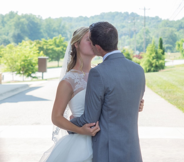 Just-married couple kissing in a garden surrounded by hills and greenery under the sunlight