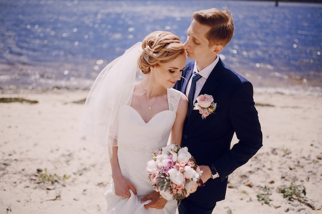 Just-married couple posing next to the seashore