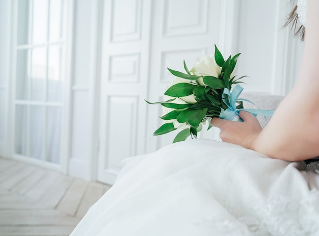 Just married couple with bouquet of white roses in studio
