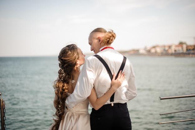 Молодожены счастливые мальчик и девочка обнимают друг друга на пирсе на озере. концепция свадьбы