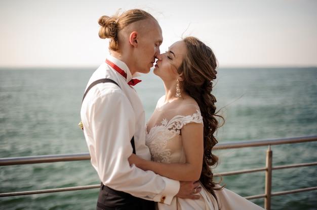 Молодожены счастливые мальчик и девочка целуются друг с другом на пирсе на озере. концепция свадьбы