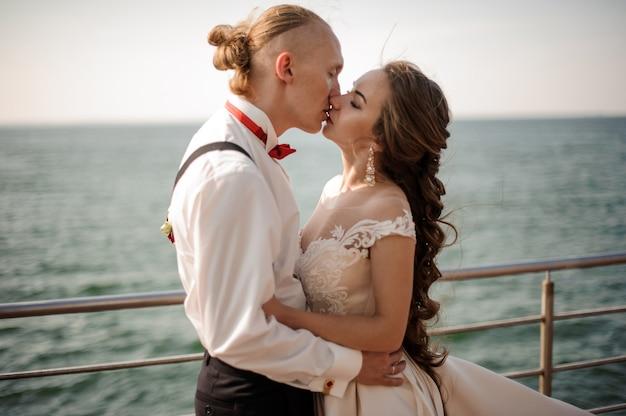 Молодожены счастливые мужчина и женщина целуются друг с другом на пирсе на озере. концепция свадьбы