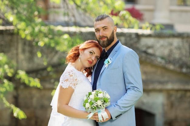 Молодожены молодоженов в свадебном платье и костюме в парке