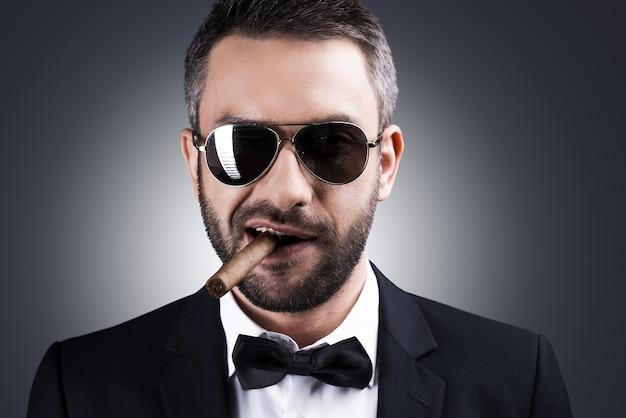 私と私の葉巻だけ。葉巻を吸って灰色の背景に立って笑っている正装とサングラスのハンサムな成熟した男の肖像画