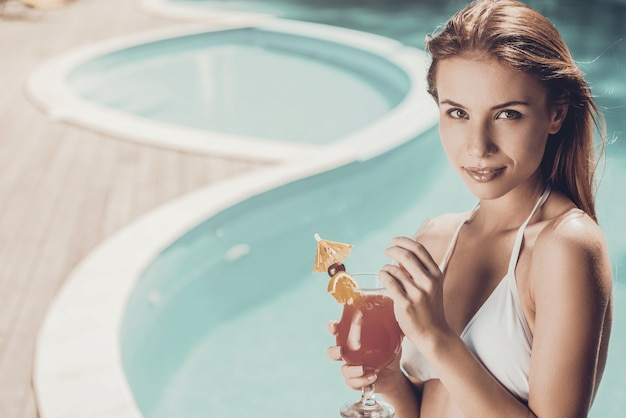 Just me and my summer cocktail. beautiful young woman in white bikini holding cocktail and looking at camera while relaxing poolside
