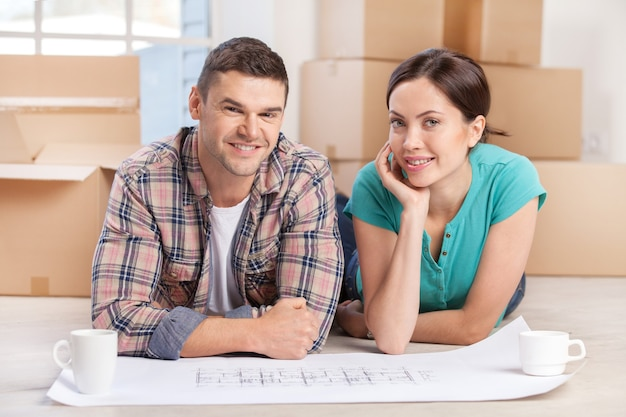 Just moved in. cheerful young couple lying on the floor with a blueprint on it while cardboard boxes laying on the background
