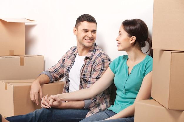 Только что переехал в новую квартиру. красивая молодая влюбленная пара сидит на полу и держится за руки, пока картонные коробки лежат вокруг них