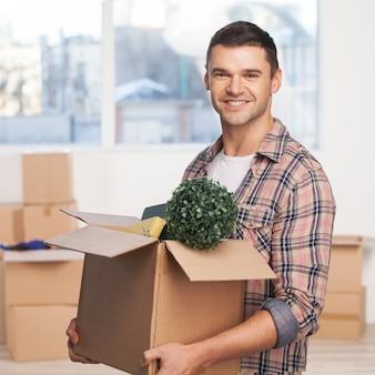 Только что переехал в новую квартиру. веселый молодой человек держит открытую картонную коробку и улыбается в камеру, пока другие картонные коробки лежат на фоне