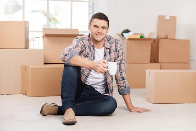 Только что переехала в новый дом. веселый молодой человек сидит на полу и держит чашку кофе, пока картонные коробки лежат на заднем плане