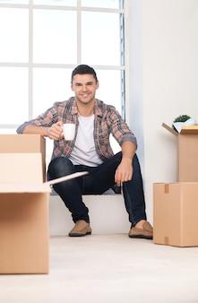 Только что переехала в новый дом. веселый молодой человек сидит на подоконнике и держит чашку кофе, пока картонные коробки лежат рядом с ним