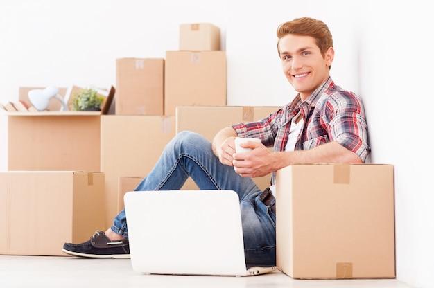 Только что переехал. вид сбоку на веселого молодого человека, сидящего на полу своей новой квартиры и пьющего кофе, а на заднем плане лежат картонные коробки.
