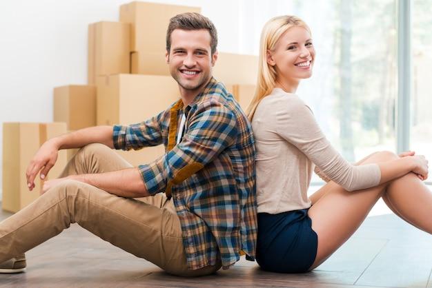 방금 새 아파트로 이사했습니다. 배경에 판지 상자가 놓여 있는 동안 새 아파트 바닥에 앉아 있는 쾌활한 젊은 부부