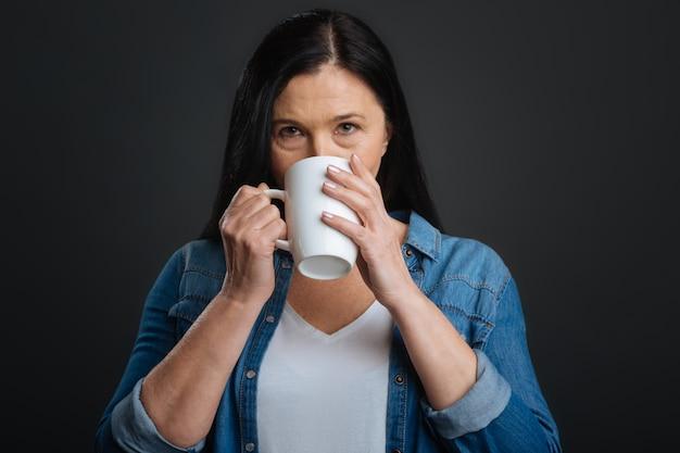たった一口。一杯のコーヒーを保持し、灰色の背景に孤立して立っている間それをすすりながら見事なかなり魅力的な女性