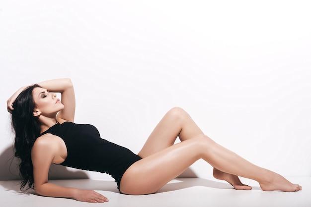 완벽 해. 검은 수영복을 입은 매력적인 젊은 여성이 머리에 손을 잡고 흰색 배경 앞에 누워 있는 동안 눈을 감고 있는 모습