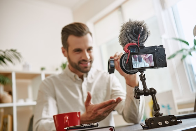 새로운 것을 기록하는 동안 카메라에 스마트 시계 신발을 보여주는 완벽한 미소 기술 블로거