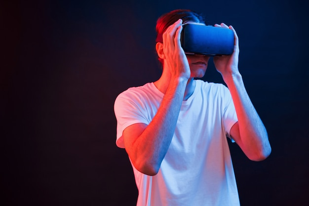 Just putting the eyewear. young man using virtual reality glasses in the dark room with neon lighting