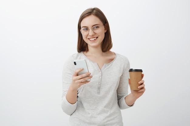 Просто нужен ответ. очаровательная беззаботная милая европейская женщина в очках держит бумажный стаканчик с кофе, пьющим напиток, наслаждается разговором с боссом и набирает сообщение в смартфоне над серой стеной