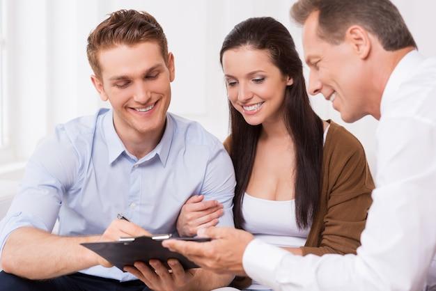 Просто подпишитесь здесь. счастливая молодая пара подписывает документы, пока уверенный зрелый мужчина держит буфер обмена и улыбается