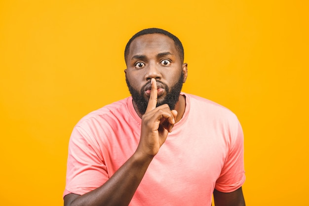 Just don't speak! close up portrait of handsome cheerful mysterious afro american silent man making hush gesture, isolated on yellow wall.