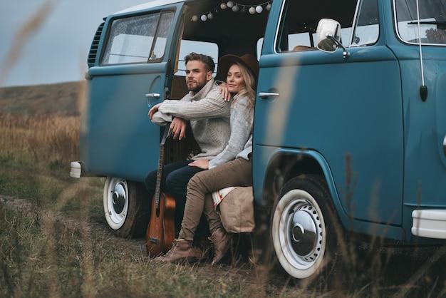 경치를 즐기기 위해 멈췄습니다. 파란색 복고 스타일 미니 밴에 앉아있는 동안 멀리보고 웃 고 아름 다운 젊은 부부