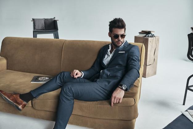 時間をかけてすべてを考え直すだけです。自宅のソファに座って目をそらしている完全なスーツを着た思いやりのある若い男