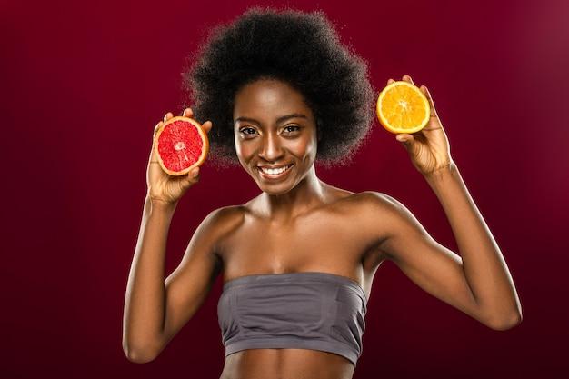 Просто попробуй. обрадованная милая женщина показывает вам свежие фрукты, пропагандируя здоровый образ жизни