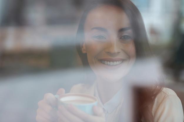 Только проснулся. рад, что красивая нежная женщина держит чашку, глядя в сторону и смеясь