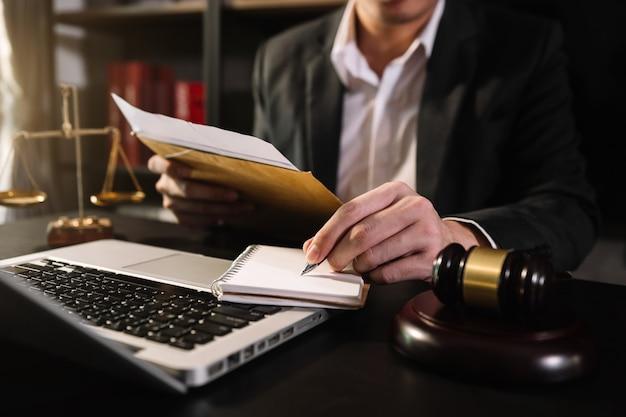 正義と法律の概念:朝の光の中でテーブルの上で、コンピューターとドッキングキーボード、眼鏡を使って、小槌を持って法廷で裁判官