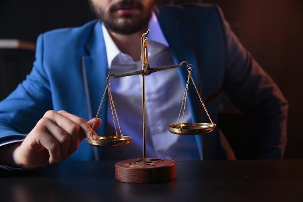 정의와 법률 개념입니다. 반영 된 나무 테이블에 황동 규모와 사무실에서 남성 변호사
