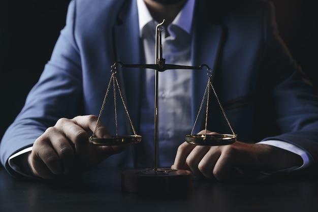 正義と法律の概念木製のテーブルに真鍮のスケールを反映したオフィスの男性弁護士