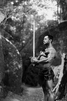 정의는 그의 유일한 규칙입니다. 숲의 바위 근처에 서 있는 검을 들고 있는 강하고 용감한 젊은 검투사의 수직 흑백 사진