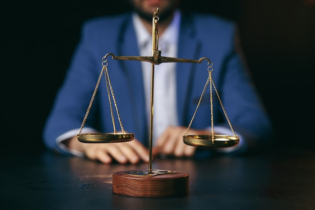 Justice and law concept.male lawyer in the office with brass scale on wooden table,reflected view