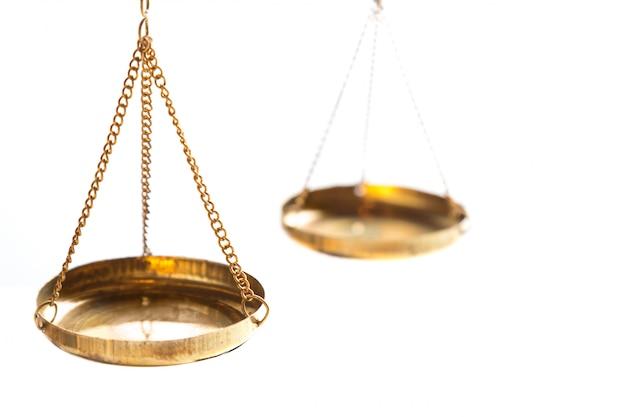 正義法裁判官は、白い背景の真鍮バランススケールを判断します。