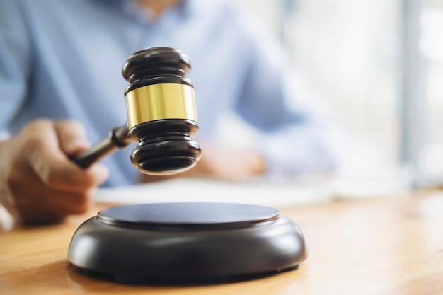 正義の法律事務所またはオークションのコンセプト。ハンマーを手に持った裁判官は、公正な判断のための討論室でテーブルの上にあります。