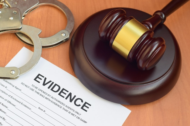 Justice mallet and evidence report blank document for crime scene investigation with police handcuffs