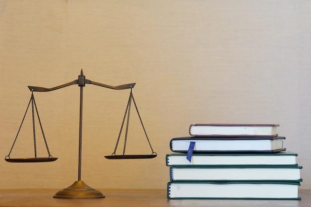 正義のスケールと空きスペースのグラデーションの背景で本を積み重ねる