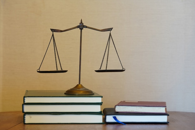 Justice scale on pile of books in gradient white and brown background
