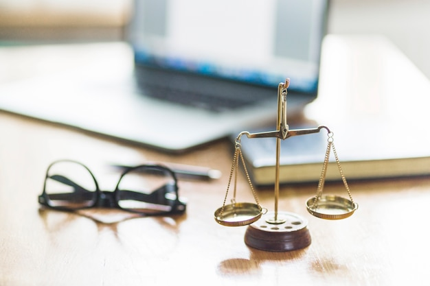 Justice scale and spectacles on wooden desk in courtroom