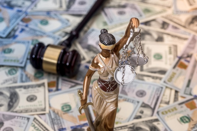 Justice scale and wooden hammer on dollar bills