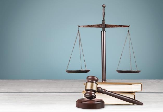正義のはかりと本と木製のテーブルのガベル