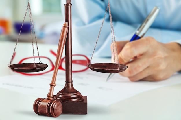 正義のはかりと木製のガベルと木製のテーブルで働くビジネスマン